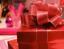 Close-up of a square shiny red gift box with gritter red ribbon bow, selective focus. And blurred background Stock Photo