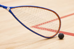 Close up of a squash racket and ball over wooden background. Playing squash on squash court Royalty Free Stock Image