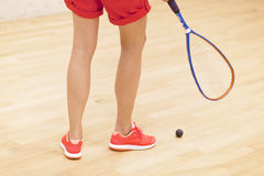 Close up of a squash racket and ball over wooden background Royalty Free Stock Images