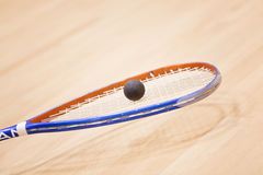 Close up of a squash racket and ball over wooden background. Playing squash on squash court Stock Image