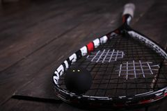 Close up of a squash racket and ball on the wooden background.  stock photography