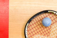 Close up of a squash racket and ball on the wooden background royalty free stock photos