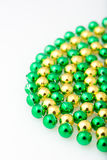 Close up st. patricks day beads in gold and green colors. St. patricks day beads in gold and green colors, close up and isolated on white background, vertical Stock Photos