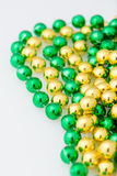 Close up st. patricks day beads in gold and green colors. St. patricks day beads, close up and isolated on white background, vertical Royalty Free Stock Images
