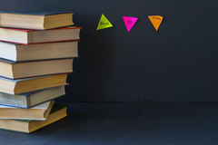 Close-up of a stack of books in hard bindings on black background. Place for text, concept of starting school, back to stock photo