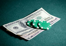 Close-up stack of casino chips and dollar bills on the poker table Stock Photo