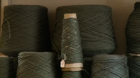 Several grey green cones of yarn for weaving. Close up of a stack of grey green yarn cones ready to be used on a loom for weaving stock video footage