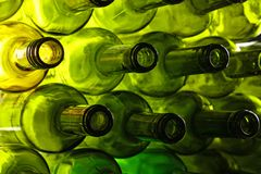 Empty green glass wine bottles isolated on white. Close up stack of many empty washed green glass wine bottle necks, low angle side view Royalty Free Stock Image