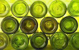 Empty green glass wine bottles isolated on white. Close up stack of many empty washed green glass wine bottles bottom side, low angle view Royalty Free Stock Images