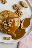 Close up stack of pancakes with caramel and nuts with spoon royalty free stock photo