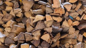 Stacked chopped firewood partly with snow royalty free stock image
