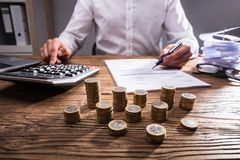Businessperson Using Calculator For Calculating Bill. Close-up Of Stacked Coins In Front Of Businessperson`s Hand Using Calculator For Calculating Bill royalty free stock image