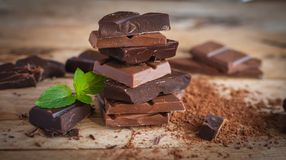 Close-up of stacked dark and milk chocolate with fresh mint, on wooden background stock image