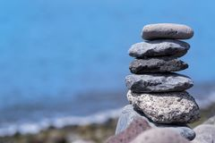 Close-up of stacked stones against coastline and blue water. Portuguese island of Madeira royalty free stock photo