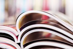 Close up stacking of opened magazine with blurry bookshelf backg. Round , extremely shallow DOF Royalty Free Stock Photography