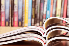 Close up stacking of opened magazine with blurry bookshelf backg Stock Image