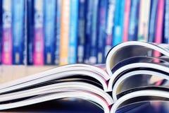 Close up stacking of opened magazine with blurry bookshelf backg Stock Photos