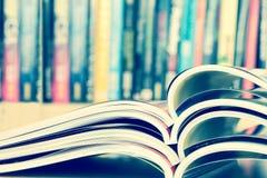 Close up stacking of opened magazine with blurry bookshelf backg Royalty Free Stock Photo