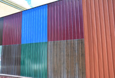Close up on stacks of various colorful metal fence panels and metal roof sheets for sale. stock image