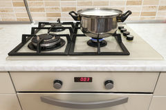 Close-up of stainless steel cooking pot on gas stove in contempo. Rary upscale modern  home kitchen. Selective focus on pot Stock Image