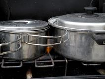 Close up of stainless steel sauce pans on a camp stove with flames licking their sides Stock Photography
