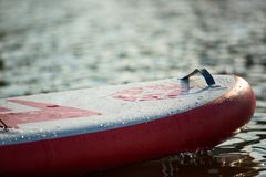 Close up of a stand up paddle board SUP and paddle on a dock. On water stock photo