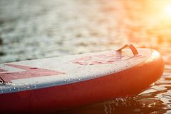 Close up of a stand up paddle board SUP and paddle on a dock. On water stock images