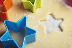 Close up star shaped cookie cutters in dough Royalty Free Stock Images