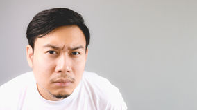 Close up staring at the camera. An asian man with white t-shirt and grey background stock image