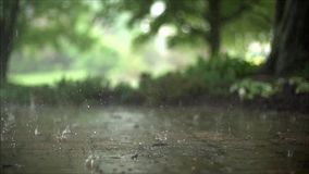 Fascinating close up steady satisfying slow motion shot of downpour rain drops falling on pavement asphalt concrete road. Close up steady slow motion shot of stock footage