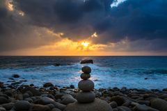 Nature Seascape with Zen Stacked Rocks on Beach in Little Sunshine at Sunrise stock images