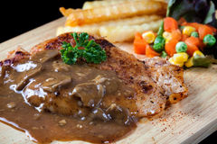 Close up steak pork with mushroom sauce, french fries and salad Stock Image