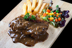 Close up steak pork with mushroom sauce, french fries and salad Stock Photography