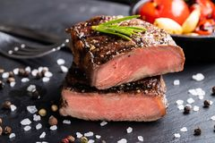 Close-up of steak Top Blade roasting medium ready to eat on dark stone background.  royalty free stock images