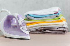 Close up steam iron colorful clothes washed laundry on white background. Housekeeping. Copy space advertisement. Place for text.