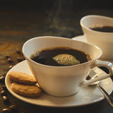 Close up of steaming coffee served in porcelain Stock Photo