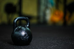 A close-up of steel black kettlebell on a blurred background. A kettlebell on a gym floor. Copy space. Stock Images