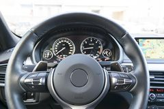 Close up of steering wheel. Car dashboard. Navigation screen. Modern car interior details Stock Photos