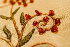 Close-up stems with curls and leaves, embroidered with satin stitch, with sewn red beads-rings. Royalty Free Stock Images