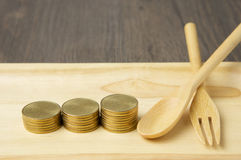 Close up step of gold coins and spoon with fork Stock Photos