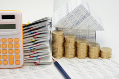 Close up step pile of gold coins and house. With pencil and pile overload document with colorful paperclip and calculator on finance account with white Royalty Free Stock Photography