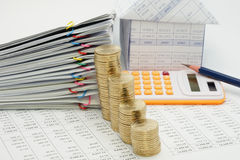 Close up step pile of gold coins. And pile overload document with colorful paperclip and house with pencil and calculator have blur on finance account with royalty free stock photo