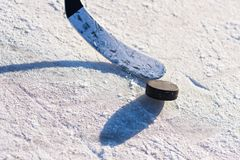 Close-up of sticks and pucks in the stadium. Close-up stick and puck on the ice background Royalty Free Stock Photography