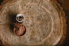 Close-up of a sticks of cinnamon, cocoa and star anise in a cup, on a wooden background on a stump, a place for text, a set stock photo