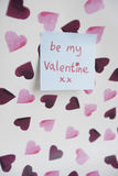 Close-up of sticky note with a orthographic message over heart shaped background Stock Photo