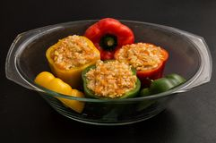 Close up, still life. Stuffed bell peppers spread in a transparent pan for baking in the oven. Black background royalty free stock image