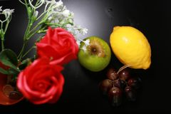 Fresh wet fruits : lemon, green apple and grapes with decoration  on black background Royalty Free Stock Photos