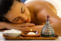 Massage oil and candle with out of focus girl in background stock photos