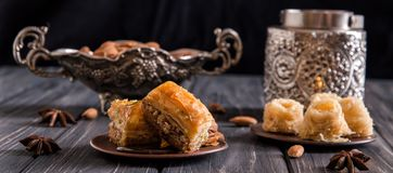 Close up. Still life. Turkish sweets. Traditional honey baklava, nuts. Pottery and silverware. Dark wooden background stock photography