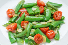 Close up, Stir fry sugar snap peas with tomato. Stock Images